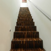 view from the ground floor of the stairs with a smoked oak cover illuminated by led inside the wall © Erika Mazza 2012